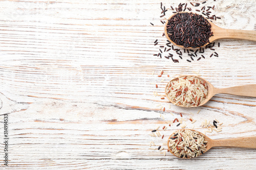 Photographie  Different sorts of rice on white wooden table, flat lay