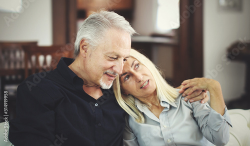 Photographie Senior couple relaxing on a sofa and talking together
