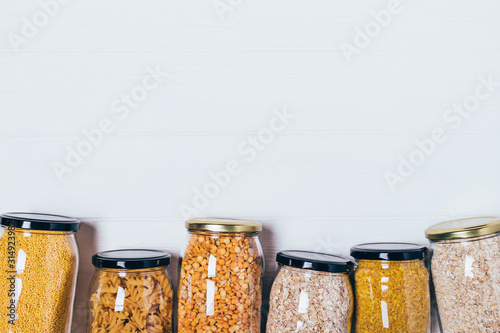 Top view glass jars with variety groats and pasta Wallpaper Mural