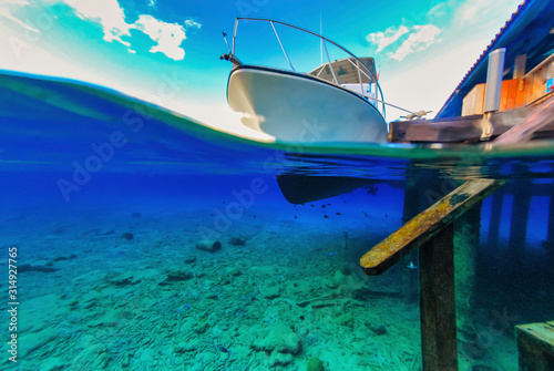 Cuadros en Lienzo  Over under view of seabed scuba diving boat and dock