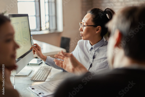 Fototapety, obrazy: Asian real estate agent using desktop PC while communicating with clients in the office.