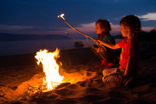 Summer Camp. Children Camping On Beach And Sitting By The Fire  On A Summer Evening