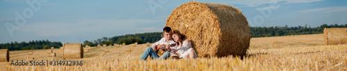 Obraz Happy young couple on straw, romantic people concept, beautiful landscape, summer season - fototapety do salonu