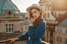 Young Elegant Fashionable Brunette Woman, Model Wearing Trendy Blue Knitted Sweater, Stylish White Hat, Wrist Watch, Earrings, Ring, Posing At Sunset, In European City. Copy, Empty Space For Text