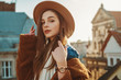 Elegant fashionable brunette woman, model wearing stylish hat, wrist watch, blue sweater, brown faux fur coat, posing at sunset, in European city. Copy empty space for text