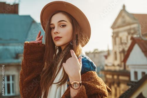Billede på lærred Elegant fashionable brunette woman, model wearing stylish hat, wrist watch, blue sweater, brown faux fur coat, posing at sunset, in European city