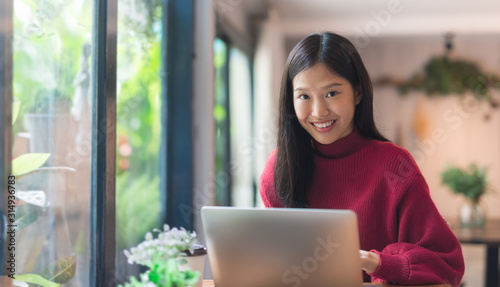 Fototapety, obrazy: Happy young Asian girl working at a coffee shop with a laptop .Woman happy smiling to camera in cafe day