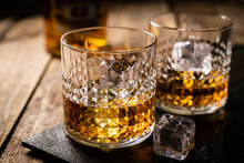 Whiskey In Glasses On Wood Bac...