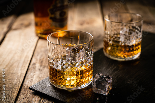 Whiskey in glasses on wood background, copy space, toned Poster Mural XXL