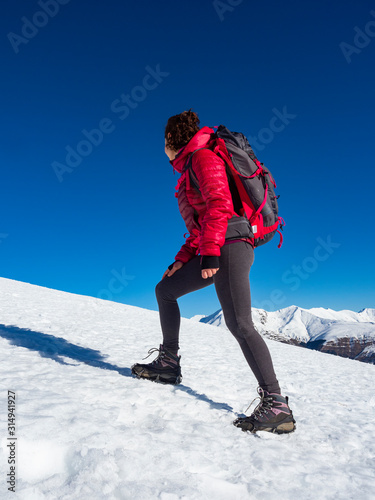 Woman hiker on a glacier with crampons on boots Canvas Print