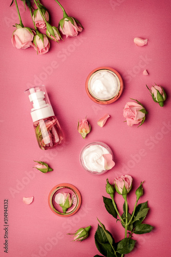Homemade spa with rose cosmetic set, cream, rose water on pink background top...