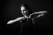 A Sensual Portrait Of A Woman In A Low Key. Brunette Model. Photo Session In The Studio. Dark Background. Lady In Black. Monochrome Photography