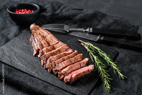 Fototapeta Roasted medium rare sliced flank beef steak. Black background. Top view obraz
