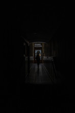 Silhouette Of A Person In The Middle Of A Passageway Inside A Dimly Lit Building