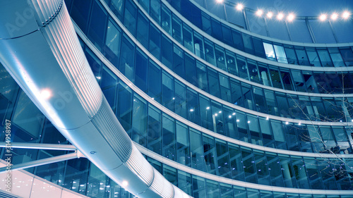 Fototapeta Night architecture - building with glass facade. Modern building in  business district. Concept of economics, financial. Photo of commercial office building exterior. Abstract image of office building obraz