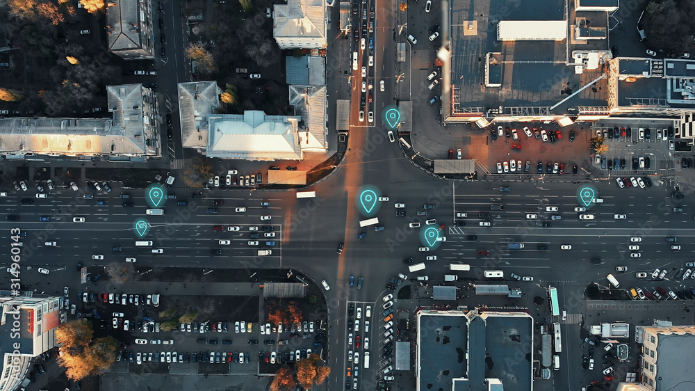 Fototapeta Aerial view of city intersection with many cars and GPS navigation system symbols. Autonomous driverless vehicles in city traffic. Future transportation concept.
