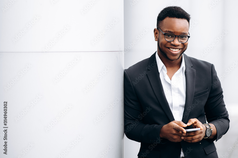 Fototapeta Attractive african american businessman in stylish suit is smiling with phone in his hands, outdoors