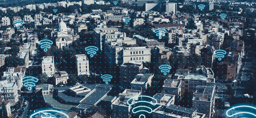 Digital city of future concept. Aerial view of European cityscape with wireless communication networks WI-FI neon symbols, IoT Internet of Things, Big Data web connections in all buildings and houses.