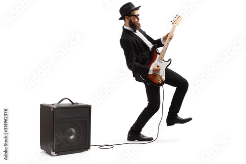 Photo Bearded male artist in a suit playing a plugged electric guitar