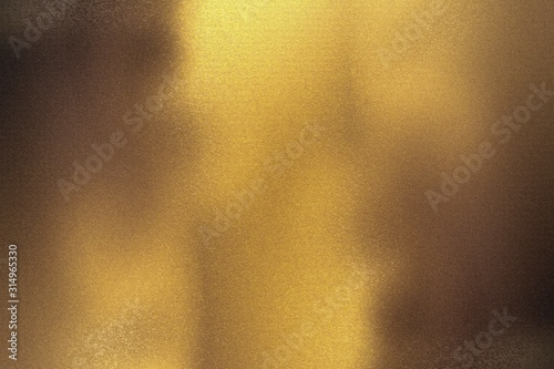 Photo Brushed bronze foil metallic wall with glowing shiny light, abstract texture bac