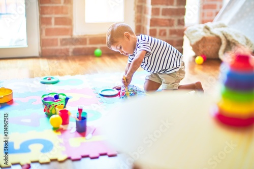 Obraz Beautiful toddler boy sitting on puzzle playing meals with plastic plates, fruits and vegetables at kindergarten - fototapety do salonu