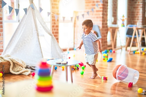 Obraz Beautiful toddler boy playing with basketball ball and plastic basket at kindergarten - fototapety do salonu
