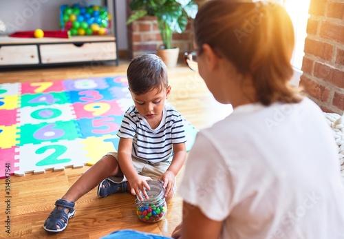 Obraz Beautiful teacher and toddler boy sitting eating small chocolate balls at kindergar - fototapety do salonu