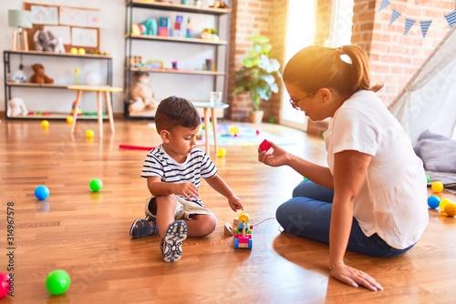 Obraz Beautiful teacher and toddler boy playing with train at kindergarten - fototapety do salonu