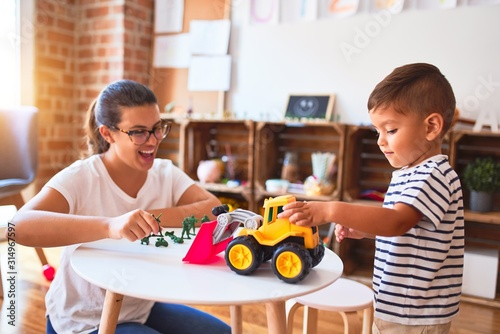 Obraz Beautiful teacher and toddler boy playing with tractor and cars at kindergarten - fototapety do salonu