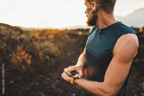 Obraz Athletic runner start training on fitness tracker or smart watch and looking forward on horizon. Trail running and active lifestyle concept. - fototapety do salonu