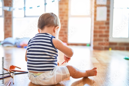 Obraz Adorable toddler playing around lots of toys at kindergarten - fototapety do salonu
