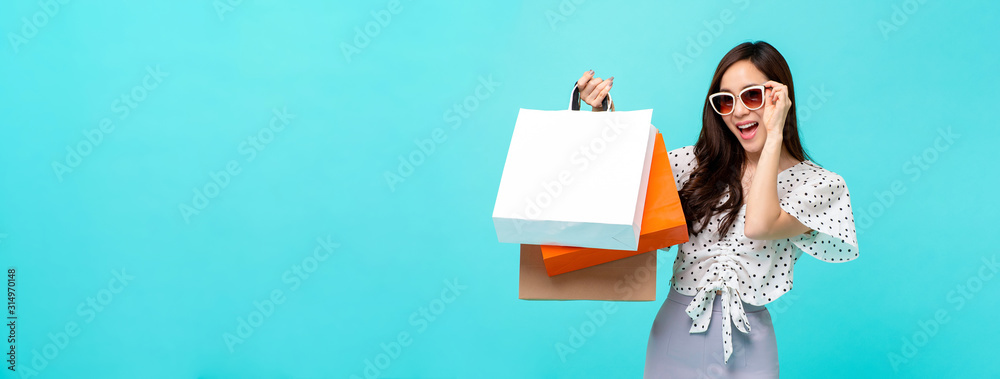 Fototapeta Happy Asian shopaholic woman carrying shopping bags in light blue banner background