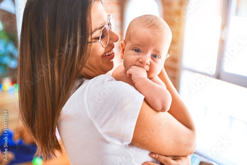 Obraz Young beautifull woman and her baby standing at home. Mother holding and hugging newborn - fototapety do salonu
