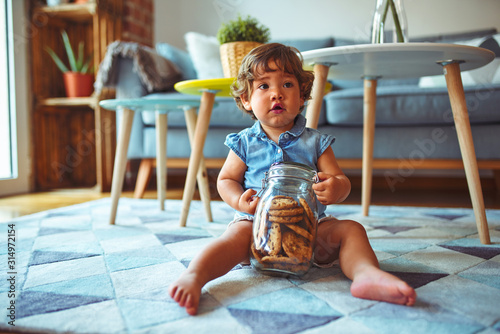 Obraz Beautiful toddler child girl holding jar of cookies sitting on the floor - fototapety do salonu