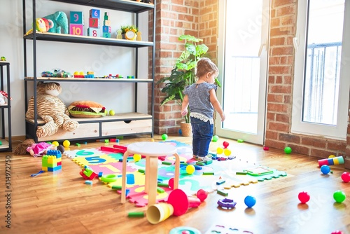 Obraz Beautiful toddler standing around lots of toys at kindergarten - fototapety do salonu