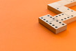 canvas print picture - Playing dominoes on a orange table. Leisure games concept. Domino effect.