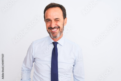 Fototapety, obrazy: Middle age businessman wearing elegant tie standing over isolated white background winking looking at the camera with sexy expression, cheerful and happy face.