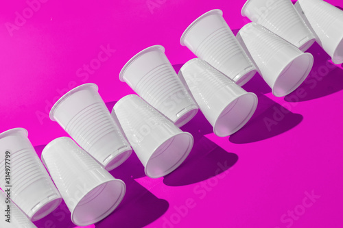 the abstract pattern of plastic cups on color surface with harsh trendy shadows Canvas-taulu