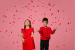 canvas print picture - Happy romantic little couple child girl and boy stand in the rain of flying rose petals on pink background. St. Valentine's Day