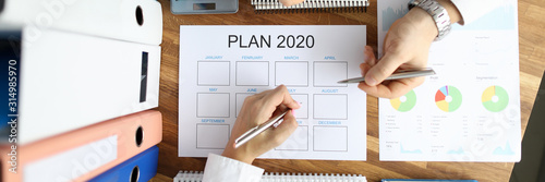 Fototapeta Two business people hold silver pen in hands against office table background. Strategy plan 2020 new year top view. Business start up concept. obraz