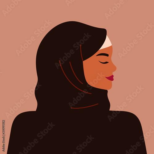 Slika na platnu Portrait of a strong muslim woman in profile wearing a black hijab
