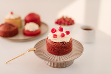 Raspberry Cupcake On Stand With A Plate Of Various Muffins On White Background