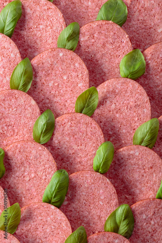 Fotografiet  Sliced smoked sausage with green basil leaves.