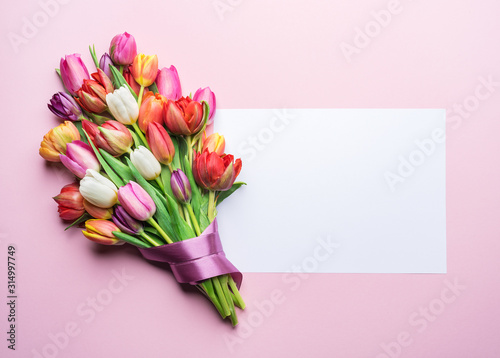 Obraz na plátně Colorful bouquet of tulips and a paper on pink background.