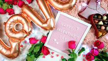 Happy Valentine's Day Flat Lay Overhead With Roses, Chocolate Gift Box And Letterboard With Greeting Text, And Large Rose Gold Balloons In Shape Of The Word Love.