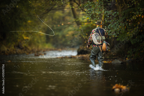 Close-up view of the hands of a fly fisherman holding a lovely trout while  fly Canvas Print