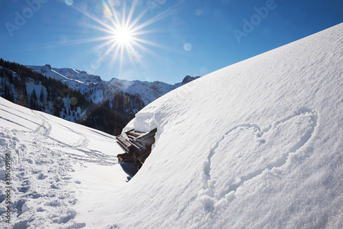 bright sunny winter landscape tirol, snow covered alp hut and love heart Canvas Print