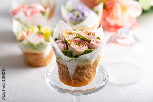 Fototapeta Flower cupcakes on white background. Beautiful sponge cup cakes decorated with buttercream roses. obraz