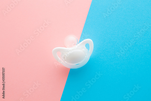Fotografie, Tablou White silicone baby soother on pastel pink blue table