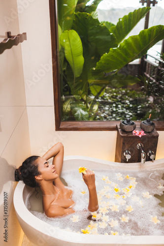 Asian woman enjoying in flower spa bath with foam, bubbles and yellow frangipani flowers Fototapete